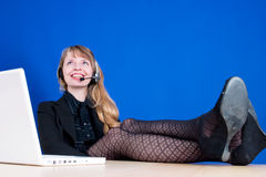 A woman with her legs on the table. A customer service representative smiling during a telephone conversation with her feet on the desk, shot against a dark blue Stock Photo