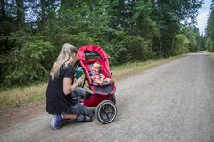 Woman playing with her little boy while jogging together on a trail Stock Images