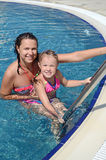 Woman and her little cute daughter have a fun in pool Royalty Free Stock Photography