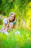 Woman and her little daughter sitting on grass Royalty Free Stock Photos