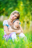 Woman and her little daughter sitting on grass Royalty Free Stock Image