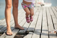 A woman and her little daughter are walking along the lake pier on a Sunny summer day, their feet close stock image