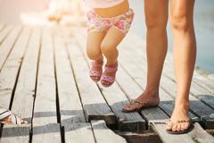 A woman and her little daughter are walking along the lake pier on a Sunny summer day stock photo