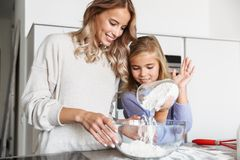 Woman with her little sister indoors at home kitchen cooking with flour. Image of a happy young women with her little sister indoors at home kitchen cooking with royalty free stock images