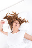 Woman with her long brunette hair spread out on the pillow Stock Image