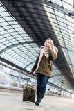 Woman with her luggage walking along the platform in train stati. On after arriving Royalty Free Stock Photos