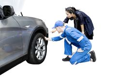 Woman with her mechanic checking a flat tire. Young women with her mechanic checking a flat tire on her car, isolated on white background Royalty Free Stock Image