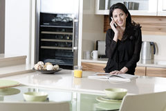 Woman on her mobile in a kitchen Royalty Free Stock Photography