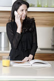 Woman on her mobile in a kitchen Stock Photo
