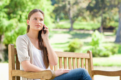 Woman on her mobile phone on a park bench Stock Image