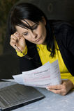Woman and her monthly bills. A brunette woman sitting at the living room table, looking with concern at her monthly bills to pay. Laptop computer used to pay Stock Photo