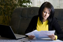 Woman and her monthly bills. A brunette woman sitting at the living room table, looking with concern at her monthly bills to pay. Laptop computer used to pay Royalty Free Stock Image