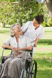 Woman with her mother sitting in wheel chair at park royalty free stock image