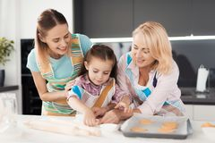 The woman and her mother are teaching the girl how to cook homemade muffins. They put dough in molds Stock Photos