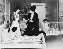 A woman with her nanny and two children in a bedroom talking with each other Stock Photos
