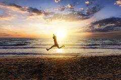 Woman during her outdoor exercise on the beach. Woman runs and jumps in the air during her outdoor exercise on the beach during sunset time royalty free stock photography