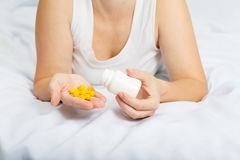 Woman in her pajamas in bed holding yellow pills Royalty Free Stock Image