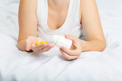 Woman in her pajamas in bed holding yellow pills Stock Image