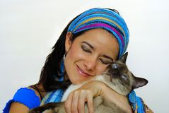 Woman and her pet cat. Young woman with bandanna dearly holding Siamese cat pet Royalty Free Stock Photo
