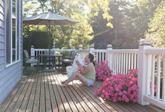 Woman and her pet dog outdoors on home deck during bright sunlight on a lovely summer morning royalty free stock image