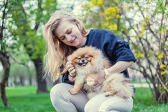 Woman with her Pomeranian puppy on her hands on a bench in the p royalty free stock photo