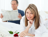 Woman with her rose while her husband is reading Stock Photo
