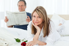 Woman with her rose while her husband is reading Stock Image