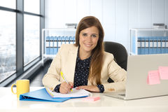 Woman on her 30s at office working at laptop computer desk taking notes Royalty Free Stock Images