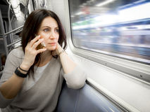 Woman in her 30s is riding the subway ans looking out the window royalty free stock image