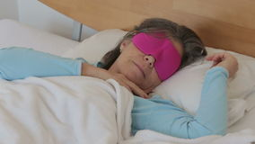 Woman in her 50s sleeping with a pink sleeping mask stock video