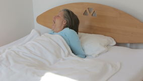 Woman in her 50s waking up in the morning and looks happy stock video