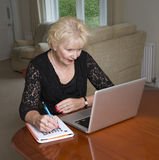 Woman in her sixties completing a crossword Royalty Free Stock Photography