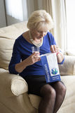Woman in her sixties and prescription drugs. Woman with a glass of water and a prescription medicine paper bag Royalty Free Stock Image