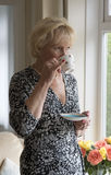 Woman in her sixties standing drinking tea Royalty Free Stock Images