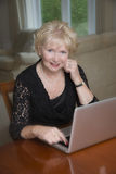 Woman in her sixties using a laptop computer Stock Photo