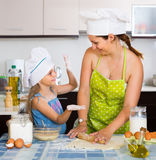 Woman and her small assistant kneading paste Royalty Free Stock Image