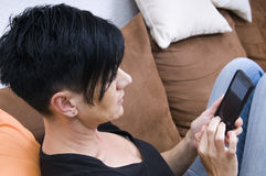 Woman an her smart phone. Head-and-shoulder view from elevated camera position of a black-haired woman of middle age on brown sofa sitting and Smartphone typing Stock Photography
