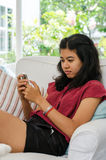 Woman with her smart phone sitting on sofa in living room Stock Photos