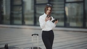 Woman with her son check-in online registration on her mobile phone in airport hall. Business woman or attractive girl in a white shirt with luggage checks stock video footage