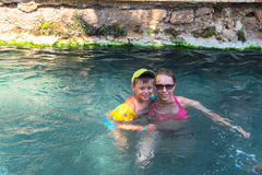 Woman and her son in Cleopatra pool. Pammukale, Turkey - July, 2015: photo of women and her son at thermal Cleopatra pool in ancient city Hierapolis, near modern royalty free stock photography
