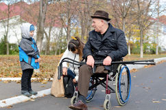 Woman and her son helping a disabled old man. Woman and her cute young son helping a disabled old men in a wheelchair with his crutches on his lap as she bends Stock Photography
