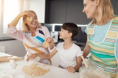 A woman, her son and her mother cook homemade cookies. They fool around, pretending that their eyes are circles of dough. A woman, her son and her mother cook Royalty Free Stock Image