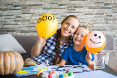 Woman and her son are hiding behind the ball. Prepare for Hallow. Woman and her son are hiding behind the ball Stock Image