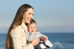 Woman and her son looking forward. Happy mother and her son looking forward on the beach royalty free stock photo