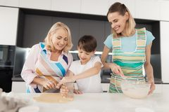 A woman, her son and her mother cook homemade cookies. The boy cuts the dough into circles using a glass. Beaker. His mother stands next to him and kneads the Royalty Free Stock Image