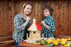 Woman and her son painting a bird house stock photos