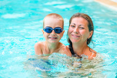 Woman with her son in the pool Royalty Free Stock Image