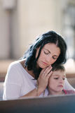 Woman with her son praying. Beautiful women with her son praying in the church Stock Photos