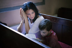 Woman with her son praying. Beautiful women with her son praying in the church stock images
