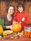 Woman and her son preparing for Halloween. Carving a pumpkin jack-o-lantern Royalty Free Stock Photos